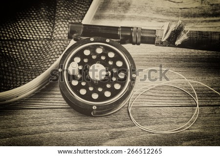 Vintage concept with grain of an antique fly fishing reel, rod, landing net and artificial flies on rustic wood. Close up with layout in horizontal format. - stock photo