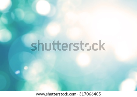 Vintage cool cyan blue green color tone blurred nature background of a view looking up through the foliage of a tree against the sky facing sun flare and bokeh: Blurred natural spring greenery bokeh  - stock photo