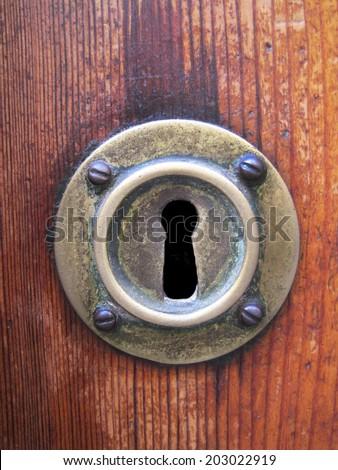 Vintage copper keyhole decorative element on weathered wooden surface - stock photo