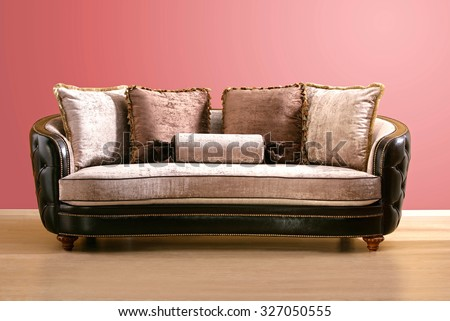 vintage couch , made of brown leather and pink velvet fabric with burgundy and pink pillow, isolated into an empty room - stock photo