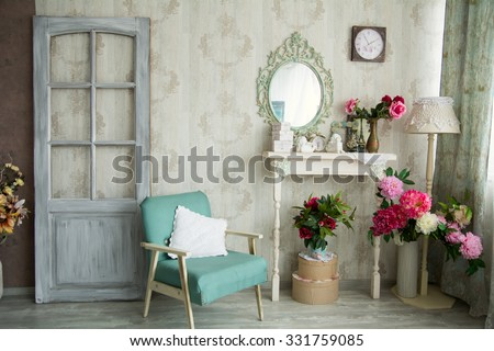 Vintage country house interior with mirror and a table with a vase and flovers. Interior design with a door and an old chair.  - stock photo