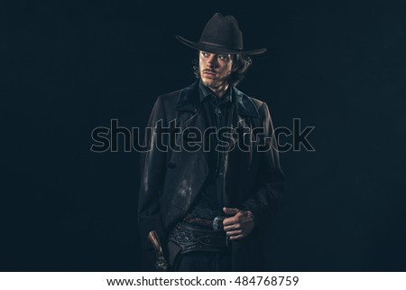 Vintage 1900 cowboy. Young man. Studio shot against dark wall.