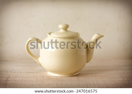 Vintage cream teapot in retro decor - stock photo
