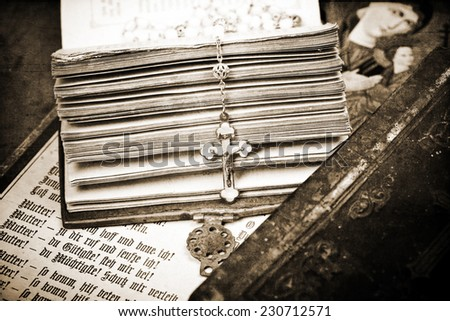 vintage crucifix on opened ancient bible, textured background, sepia,  - stock photo