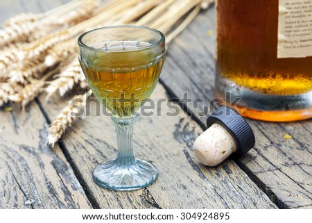 Vintage crystal brandy glass with bottle, cork and rye in the background - stock photo