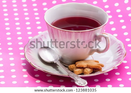 Vintage cup filled with Cranberry tea and two biscuits. - stock photo