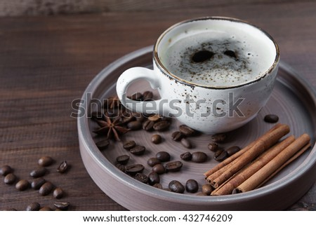 Vintage cup of coffee, coffee beans, star anise and cinnamon in a ceramic tray on a dark brown wooden background - stock photo