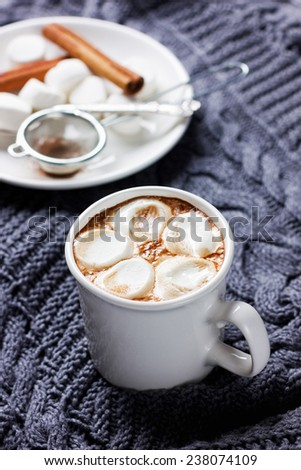 vintage Cup of hot cocoa or hot chocolate with marshmallows on a knitted sweater, christmas concept - stock photo
