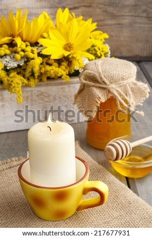 Vintage cup turned into fancy candle holder. Jar of honey in the background - stock photo