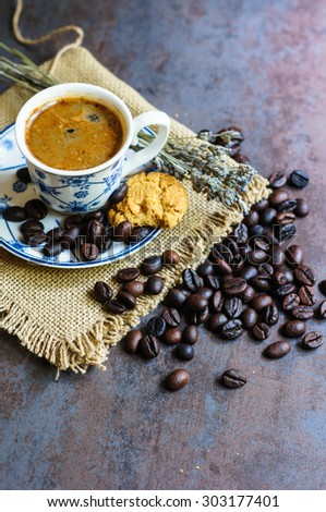 Vintage cup with black coffee, dry lavender flowers and coffee beans - stock photo