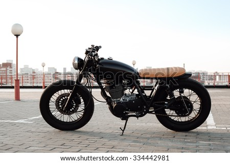 Vintage custom motorcycle in the parking lot during sunset - stock photo