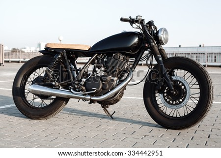 Vintage custom motorcycle in the parking lot during sunset. Road and city with open sky on background.  - stock photo