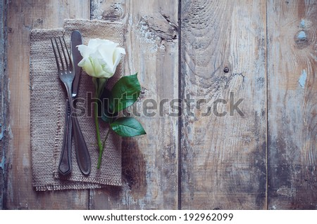 Vintage cutlery, antique silverware, fork, knife and a rose flower with rough cloth on an old wooden background - stock photo