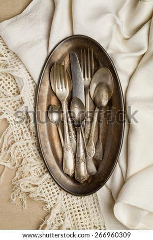 Vintage cutlery on a metal tray with a white napkin - stock photo