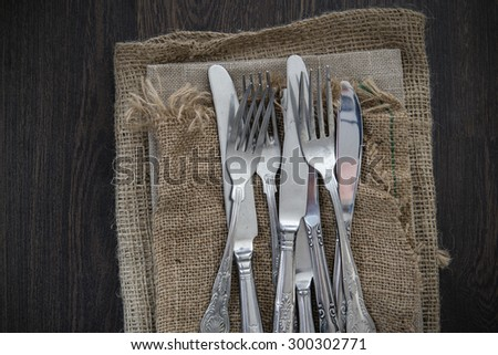 Vintage cutlery on hessian cloths on wooden background - stock photo