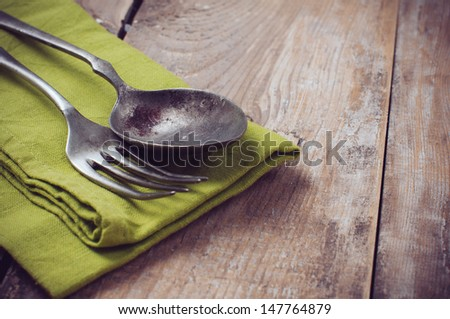 Vintage cutlery on linen napkin against a wooden board, close-up - stock photo