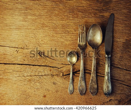 Vintage cutlery on rustic wooden background. - stock photo