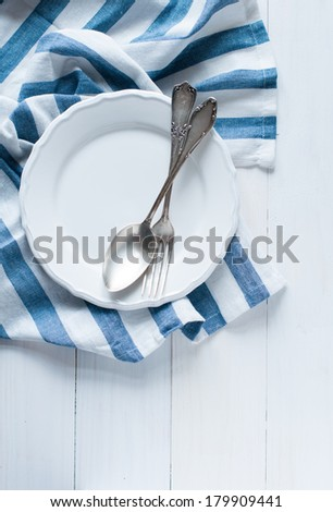 Vintage cutlery, porcelain plate and white linen napkin on wooden board, rustic style - stock photo