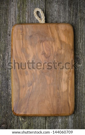 vintage cutting board with space for text on old wooden background, close-up - stock photo
