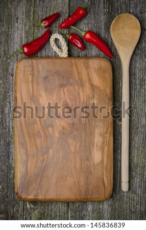 vintage cutting board with space for text, spoon and chili peppers on old wooden background, close-up - stock photo