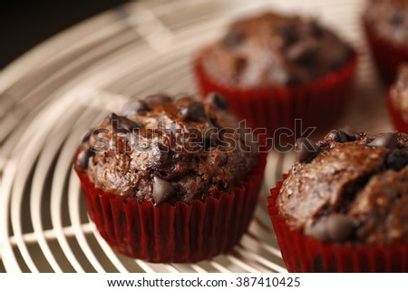 vintage dark moody shot of banana chocolate with chocolate muffins in red cups