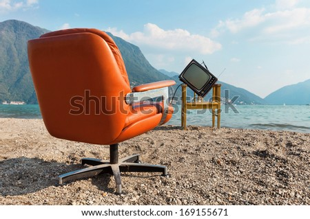 vintage decor on the lake shore, armchair and television - stock photo