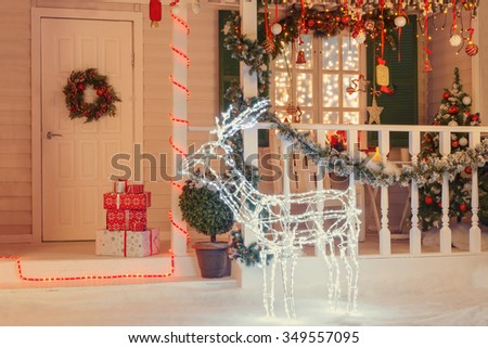 Vintage decorated Christmas building with illuminated deer - stock photo