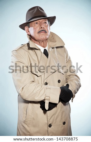 Vintage detective man with mustache and hat. Wearing raincoat. Studio shot. - stock photo