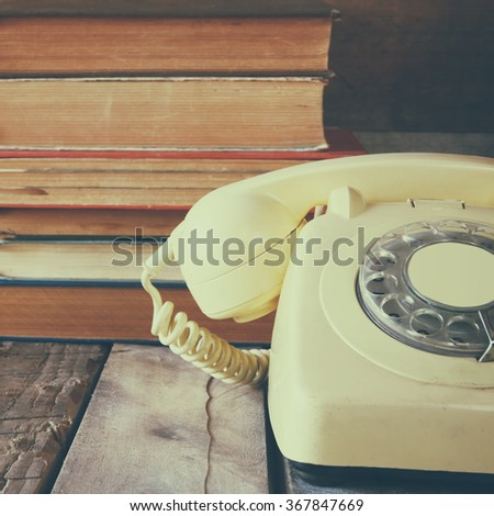 vintage dial phone next to stack of old books over wooden table  - stock photo