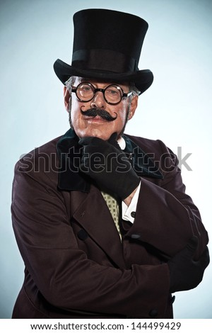 Vintage dickens style man with mustache and hat. Wearing glasses. Studio shot.