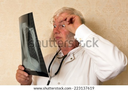 Vintage doctor examining an x-ray and looking surprised - stock photo