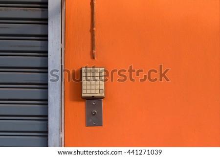 Vintage door bell button on orange wall and rolling steel door - stock photo