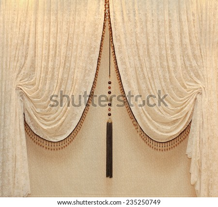 Vintage drapes with gold embellishments hanging from a wall - stock photo