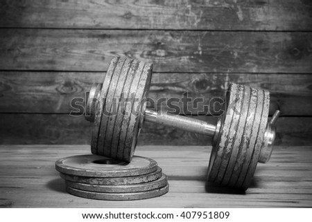Vintage dumbbell on the wooden floor. Black and white image - stock photo