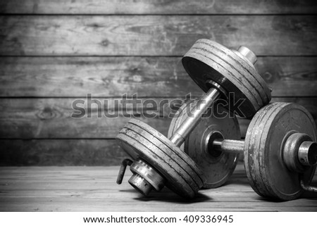 Vintage dumbbells on the wooden floor. Black and white image - stock photo