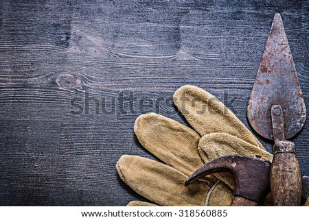 vintage dusted and rusted tools hammer and spattle on glove. - stock photo