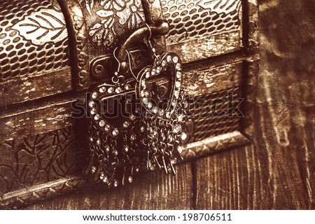 vintage earrings in a form of hearts hanging on old treasure chest - stock photo