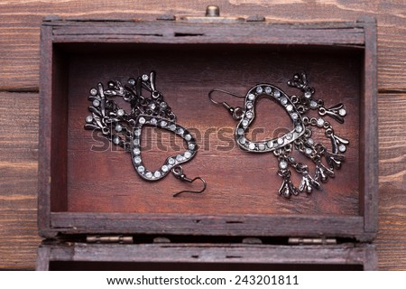 vintage earrings in a form of hearts inside old treasure chest - stock photo