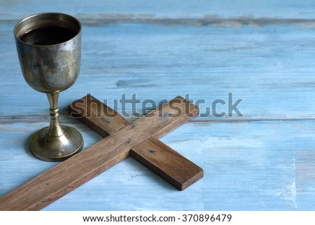 Vintage Easter cross and chalice of wine on blue background - stock photo