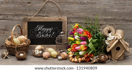 vintage easter decoration with eggs and tulip flowers. chalkboard with sample text Happy Easter! - stock photo