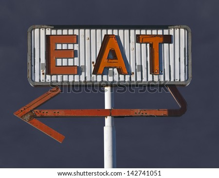 Vintage eat arrow sign in with dark storm sky. - stock photo