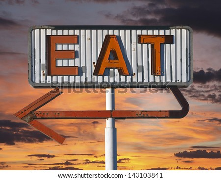 Vintage eat arrow sign in with sunset sky. - stock photo