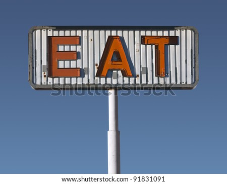 Vintage eat sign in early morning light. - stock photo