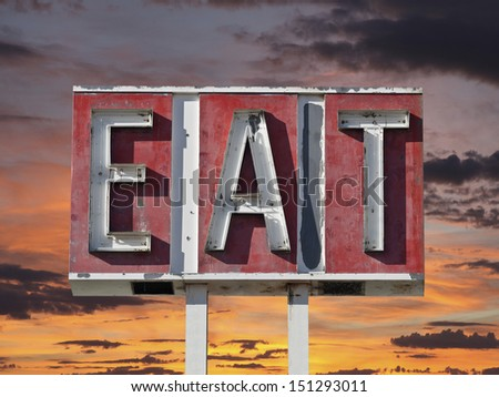 Vintage eat sign ruin with sunset sky. - stock photo
