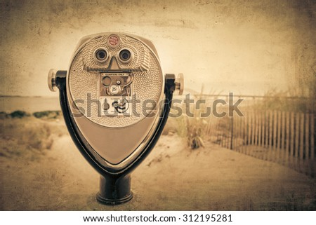Vintage effect coin operated binoculars at beach - stock photo