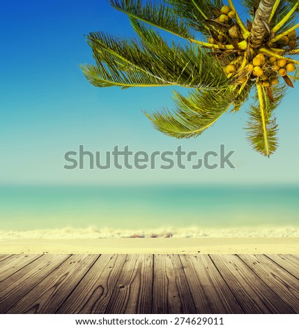 Vintage effect (retro style). Empty wooden table, coconut palm tree, ocean and blurry  beach. Tropic island background. - stock photo
