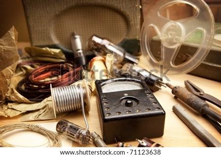 Vintage electronics. Desk top of a retro 1960s - 1970s electrician, under incandescent light . - stock photo