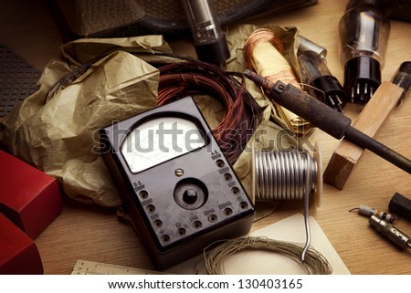 Vintage electronics. Vintage test meter and soldering equipment etc. Desk top of a retro 1960s - 1970s electrician, under incandescent light . - stock photo
