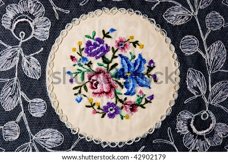 Vintage embroidery on hand made lace with a rose, a lily and other flowers and leaves. - stock photo