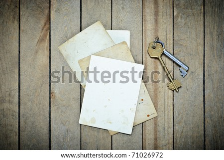 Vintage  empty photos and keys on a wooden table - stock photo